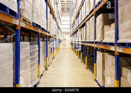 Stacks of boxes in aisle in warehouse - Stock Photo