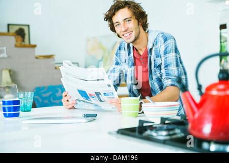 Man reading newspaper in kitchen