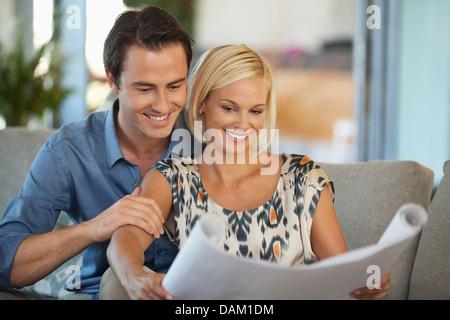Couple examining blueprints together on sofa - Stock Photo