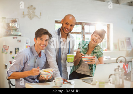 Friends having breakfast together in kitchen - Stock Photo