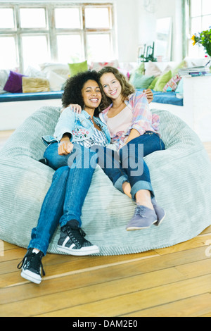 Couple watching television in beanbag chair - Stock Photo