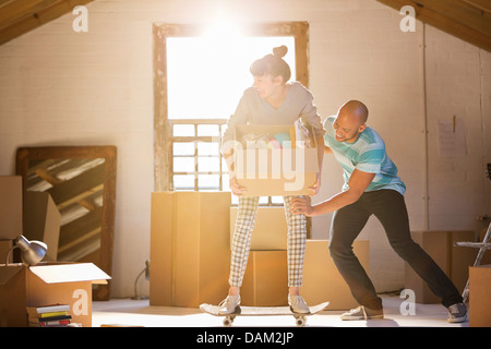 Couple unpacking boxes in new home - Stock Photo