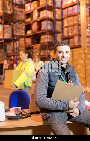 Worker smiling in warehouse - Stock Photo