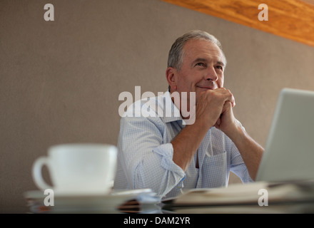 Businessman sitting at desk - Stock Photo