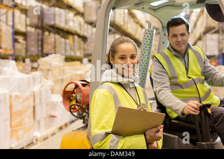 Workers smiling in warehouse - Stock Photo