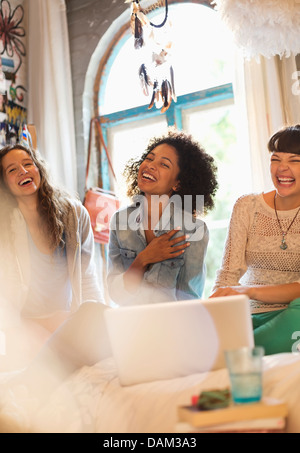 Women using laptop together in bedroom - Stock Photo