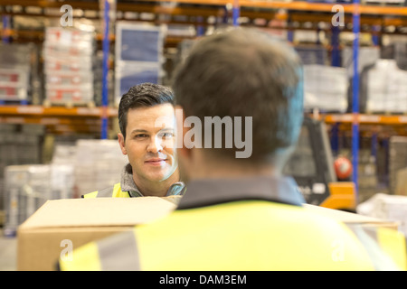 Workers carrying box in warehouse - Stock Photo