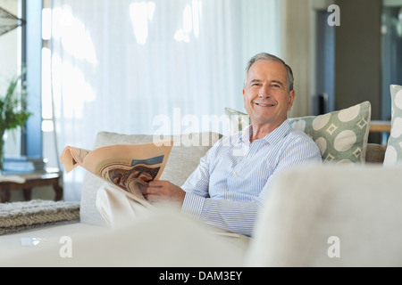 Older man reading newspaper on sofa