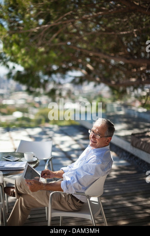 Man using tablet computer outdoors - Stock Photo
