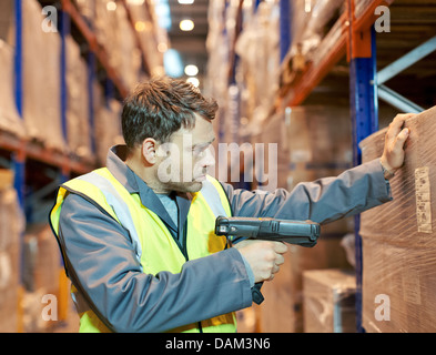 Worker scanning boxes in warehouse - Stock Photo