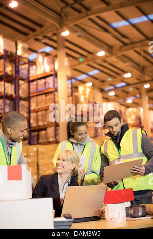 Businesswoman and workers talking in warehouse - Stock Photo