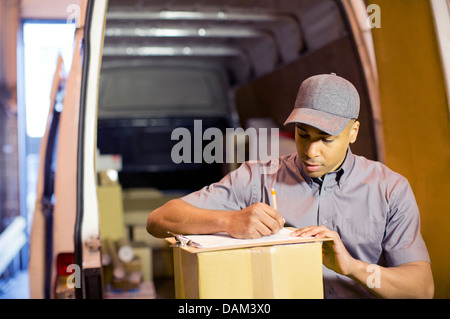 Delivery boy writing on clipboard in van - Stock Photo