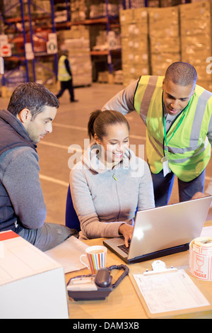 Workers using laptop in warehouse - Stock Photo