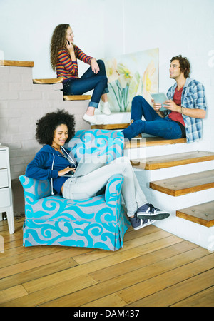 Friends relaxing together on steps - Stock Photo