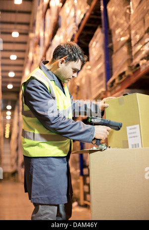Worker scanning box in warehouse - Stock Photo