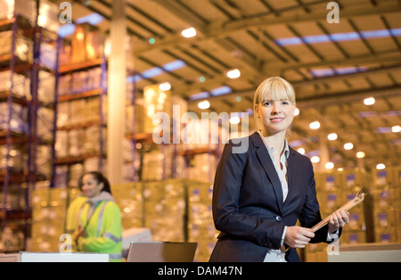 Businesswoman using clipboard in warehouse - Stock Photo