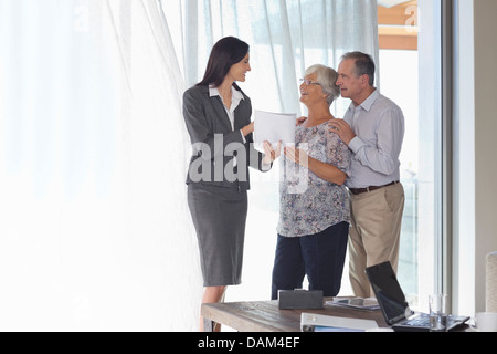 Financial advisor talking to couple in office - Stock Photo