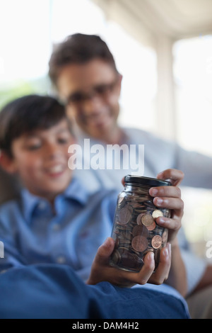Father and son holding change jar - Stock Photo