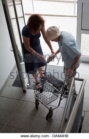 Daughter helping her old mother in walking - Stock Photo