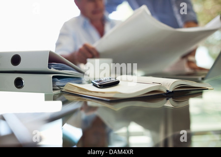 Cell phone on businessman's desk - Stock Photo