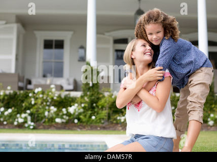 Mother and daughter hugging by swimming pool Stock Photo