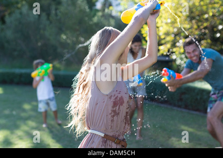 Family playing with water guns in backyard - Stock Photo
