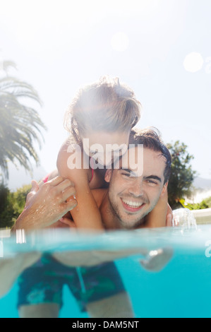 Couple playing in swimming pool - Stock Photo