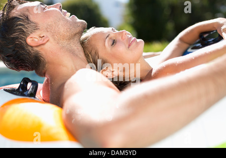 Couple relaxing in swimming pool - Stock Photo