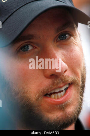 German Formula One driver Nick Heidfeld of Lotus Renault talks to journalists in the paddock at the F1 race track - Stock Photo