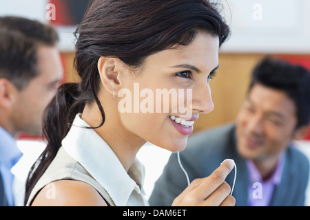 Businesswoman talking on headset in office - Stock Photo