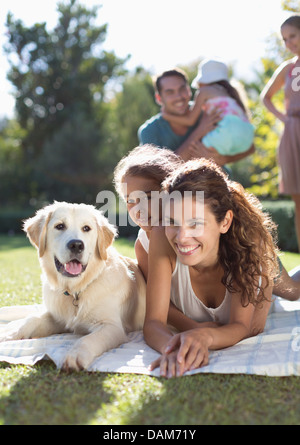 Mother, daughter and dog laying in grass - Stock Photo