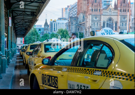 Taxi cabs line up at Flinders Street railway Station in downtown Melbourne, waiting for passengers. - Stock Photo