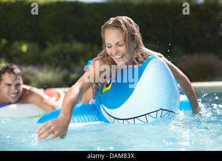 Woman playing on inflatable toy in swimming pool - Stock Photo