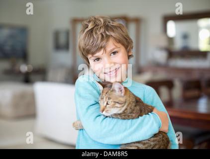 Boy hugging cat in living room - Stock Photo