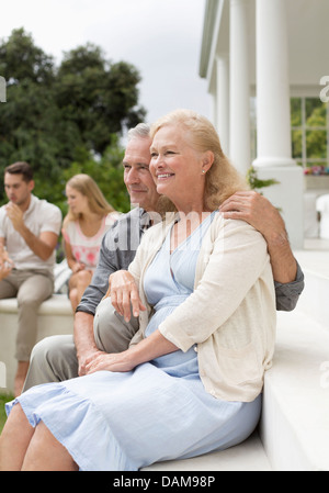 Older couple sitting on porch - Stock Photo