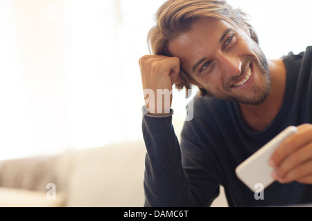 Man using cell phone on sofa - Stock Photo