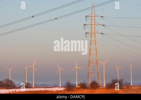 Windmills at sunset and electricity mast, Belgium - Stock Photo