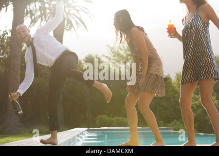 Friends having drinks by swimming pool - Stock Photo