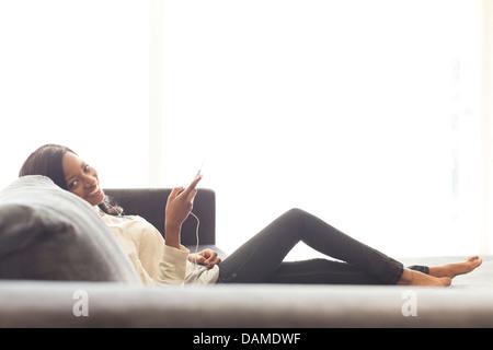 Woman listening to headphones on sofa - Stock Photo