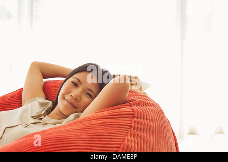 Smiling woman relaxing in beanbag chair - Stock Photo