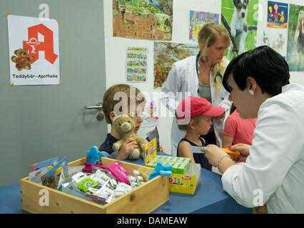 A student of medicine (r) examines the health condition of a stuffed animal in Halle(Saale, Germany, 6 June 2011. - Stock Photo