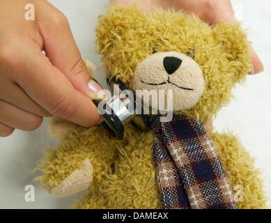 A student of medicine examines the health condition of a stuffed animal in Halle(Saale, Germany, 6 June 2011. Students - Stock Photo