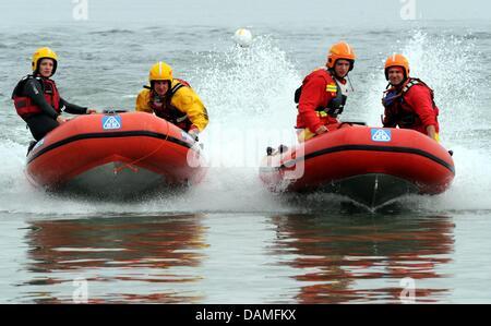 Two teams of the 'deutsche Lebens-Rettungs-Gesellschaft (DLRG)', German Life Saving Association, race with their - Stock Photo