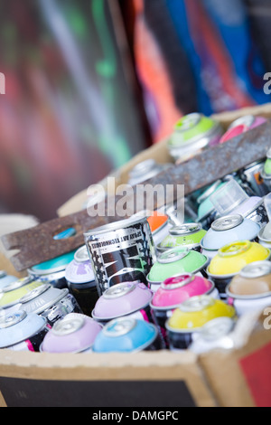 A box full of aerosol spray cans used to make graffiti. - Stock Photo