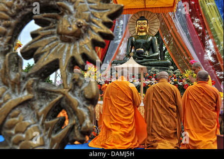 Buddhist monks kneel in front of the largest Jade Buddha worldwide inside the monastry Pagode Vien Giac in Hanover, - Stock Photo