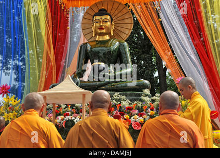 Buddhist monks stand in front of the largest Jade Buddha worldwide inside the monastry Pagode Vien Giac in Hanover, - Stock Photo
