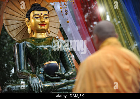 A Buddhist monk stands in front of the largest Jade Buddha worldwide inside the monastry Pagode Vien Giac in Hanover, - Stock Photo