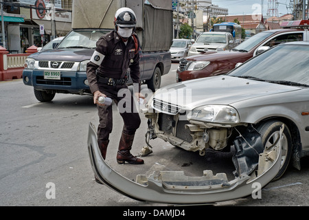 Detail of vehicle frontal damage of a car accident with policeman using spray paint to mark out position. Thailand - Stock Photo