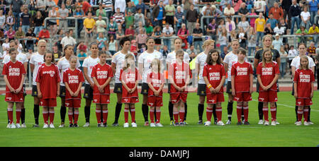 The players of the Australian National Women's soccer team stand with children before a test match at the Jahn Stadium - Stock Photo