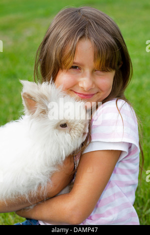 dwarf rabbit (Oryctolagus cuniculus f. domestica), seven year old girl with dwarf rabbit - Stock Photo